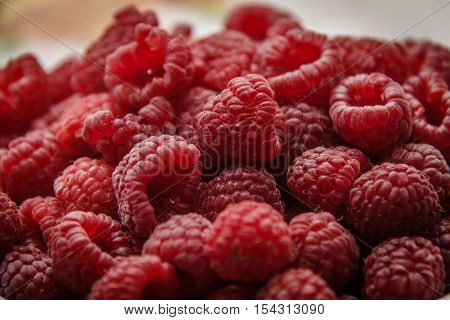 red ripe raspberry lie heaped on a table