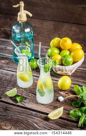 Fresh lemonade with fruit and mint on wooden table