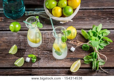 Ingredients for fresh lemonade with ice on wooden table
