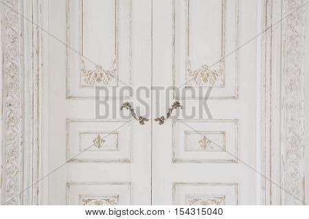 Old-style door, white old-style handle closeup. antiques interior.