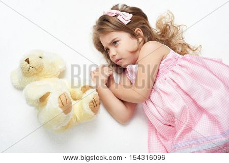angry girl child with teddy bear lie on white towel in bed, dressed in pink