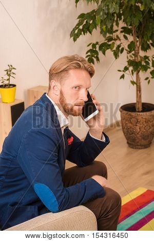 Portrait of serious confident rich European businessman speaking over mobile or smart phone with business foreing partners while staying at home.