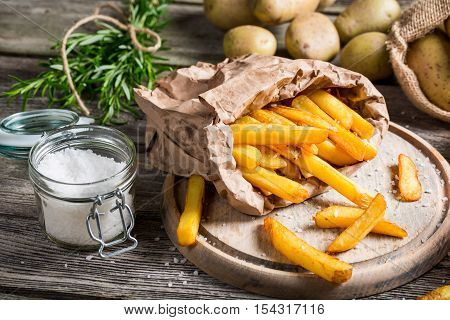 Homemade fries with salt and herbs on wooden table
