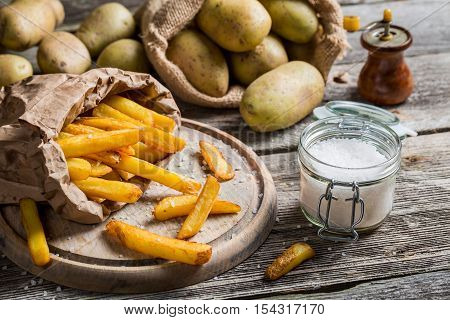 Homemade fries with salt and pepper on wooden table