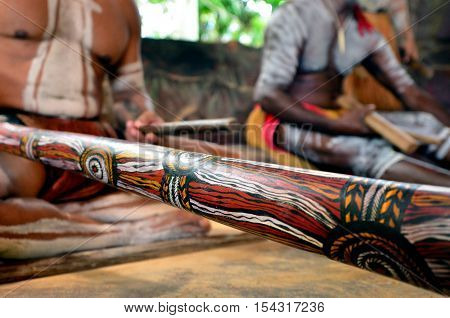 Yirrganydji Aboriginal men play Aboriginal music on didgeridoo and wooden instrument during Aboriginal culture show in Queensland Australia.