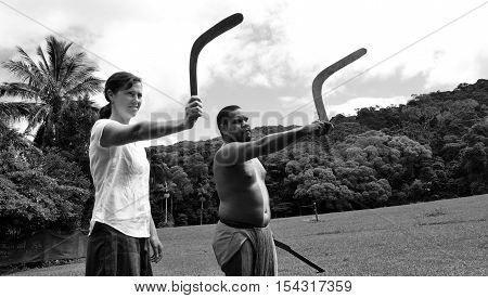 Yirrganydji Aboriginal warrior teaches a young woman how to throw a boomerang during cultural show in Queensland Australia. (BW)