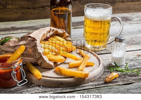 Homemade fresh fries with cold beer on wooden table
