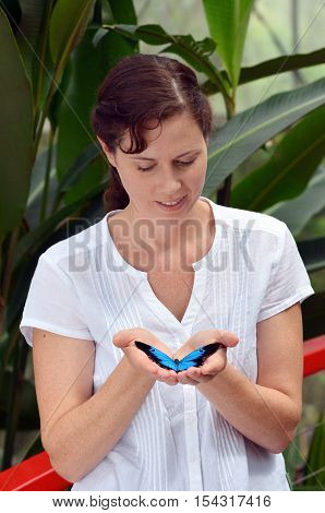 Young Woman Holds In Her Hands A Ulysses Swallowtail