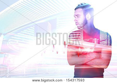 Handsome young man with folded arms and abstract heartbeat on light background with city view and copyspace. Medicine and health concept. Double exposure