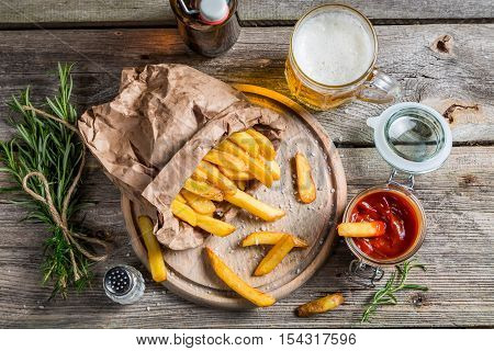Homemade fries served with beer on wooden table