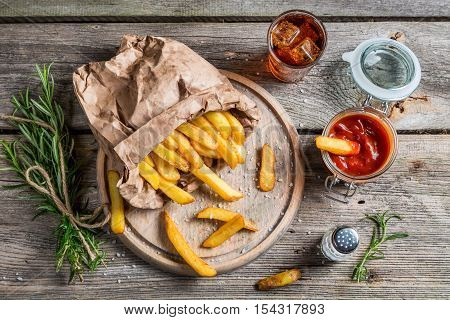 Homemade fries served with cold drink on wooden table
