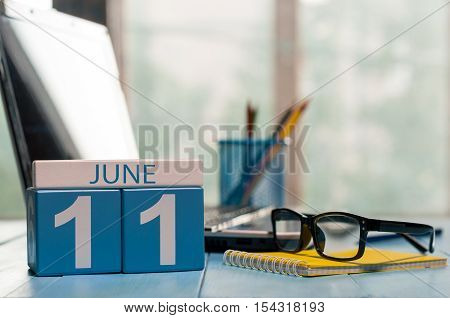 June 11th. Day 11 of month, wooden color calendar on freelance workplace background. Summer time. Empty space for text.