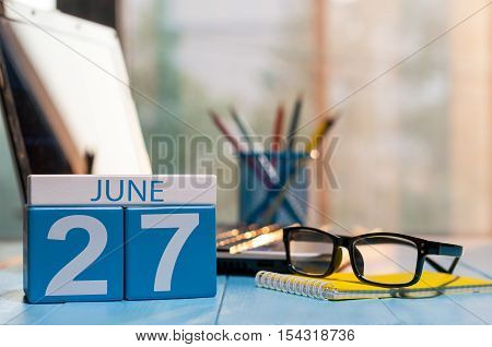 June 27th. Day 27 of month, wooden color calendar on workaholic workplace background. Summer time. Empty space for text.