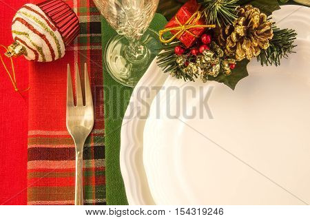 Holiday table setting with porcelain plates fork wineglass and Christmas decorations. Top view. Horizontal.
