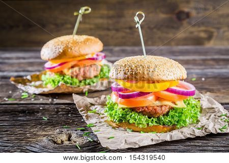 Two homemade hamburgers with fresh vegetables on wooden table
