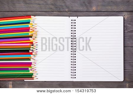 Bunch of color pencils and open notebook on gray wooden background