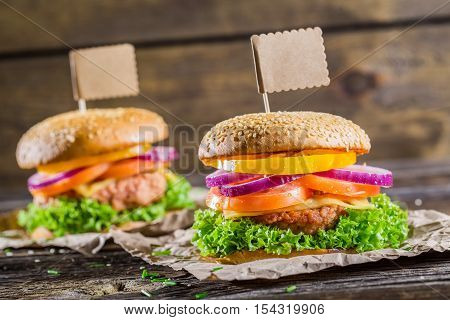 Hamburger with beef vegetables fresh herbs on wooden table