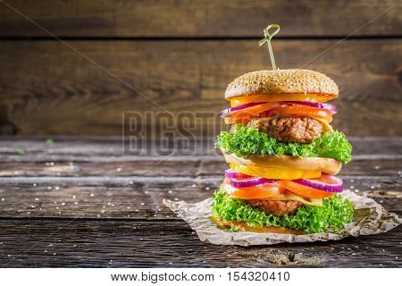 Big and tasty double-decker burger on wooden table