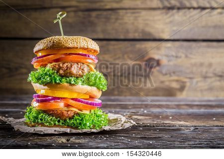 Homemade double-decker burger with vegetable on wooden table