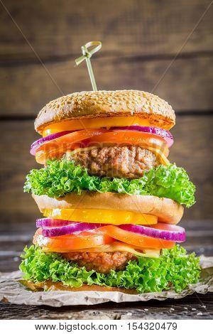 Enjoy your double-decker hamburger on wooden table