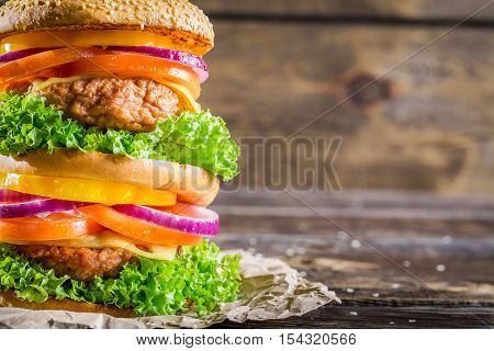 Closeup of homemade double-decker burger on wooden table