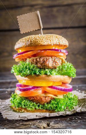 Enjoy your tasty double-decker hamburger on wooden table