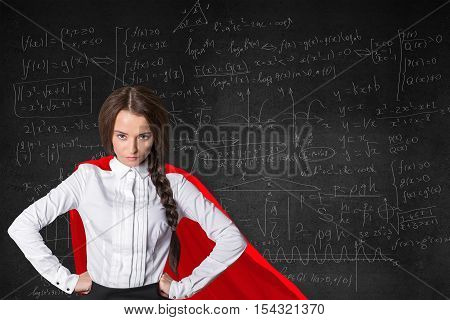 Pretty confident superwoman with red cape on mathematical formulas background. Knowledge power concept