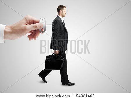 Hand turning winder on business person's back. Grey background. Control concept
