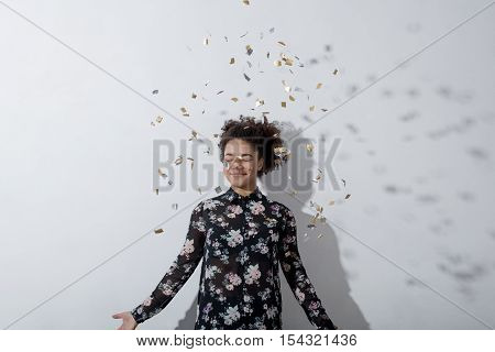 Beautiful young woman throwing confetti and looking happy indoors