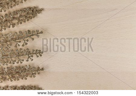 golden fern on a wooden background. shine