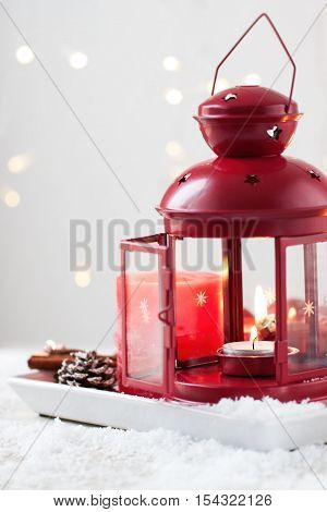 Christmas lantern with candles snow christmas decorations and fir cones closeup