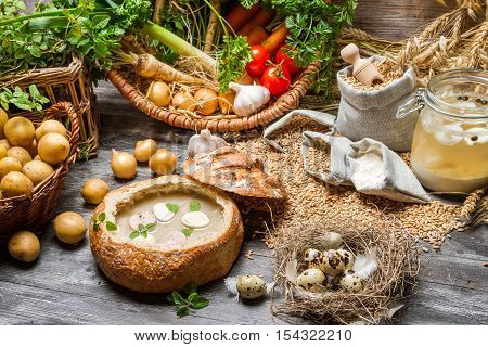 Fresh vegetables and homemade soup on wooden table