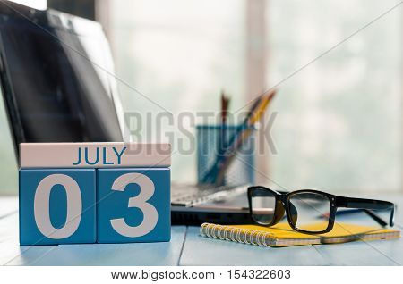July 3rd. Day of the month 3 wooden color calendar on business workplace background. Summer time. Empty space for text.