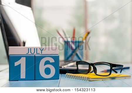 July 16th. Day 16 of month, wooden color calendar on office workplace background. Summer time. Empty space for text.