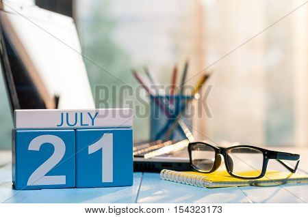 July 21st. Day 21 of month, wooden color calendar on office background. Summer time. Empty space for text.