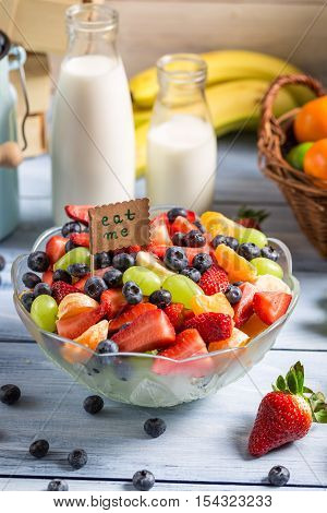 Enjoy your fresh fruit salad on wooden table
