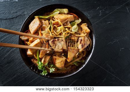 eating japanese chicken yakisoba with chopsticks in flat lay composition poster