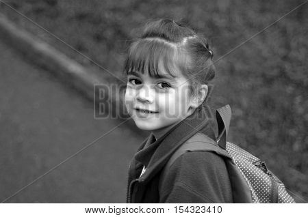 Happy Little Girl Walks To School  Looking Back Over Her Shoulder