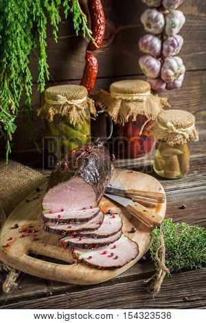 Freshly sliced smoked ham and marjoram on wooden table