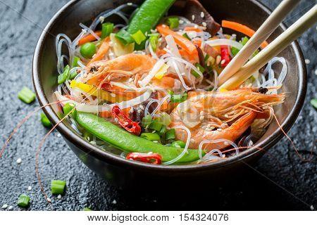 Shrimp and vegetables served with noodles on black rock