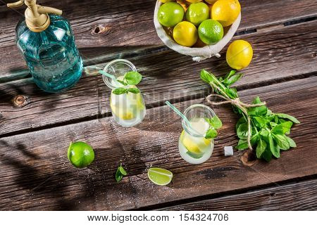 Cold summer lemonade with fresh fruit on wooden table