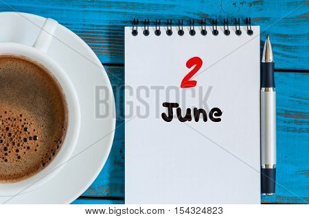 June 2nd. Image of june 2, calendar on blue background with morning coffee cup. Summer day, Top view.