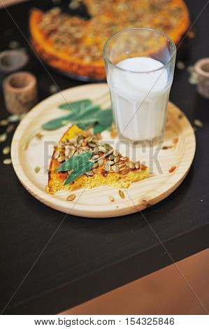 Slice of traditional pumpkin pie and a glass of natural milk for Breakfast on thanksgiving day blurred close focus.