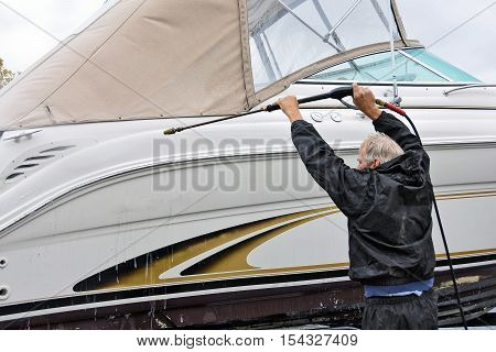 man cleaning power boat hull with pressure washer