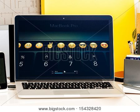 PARIS FRANCE - OCT 28 2016: Apple Computers website on new MacBook Pro Retina with OLED Touch bar in geek creative room showcasing Apple Keynote presentation of touchbar with Emoji App integration and shortcuts