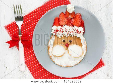 Creative idea for Christmas kid breakfast - funny santa pancake with mascarpone and strawberry