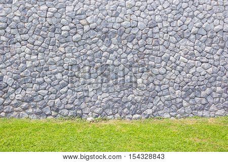 Stone brick wall background with green grass