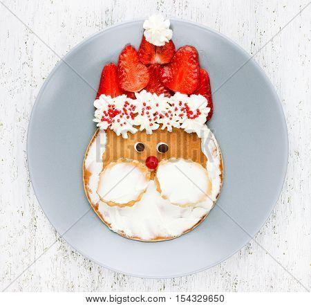 Santa pancake with strawberry for kid breakfast. Picture on the plate concept fun with food