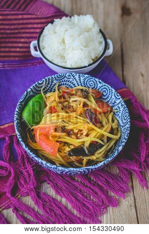 Papaya Salad with Grilled Chicken and Sticky Rice on Wood Background Thai Spicy Food on Wood Background Thai Cuisine on Wood Background