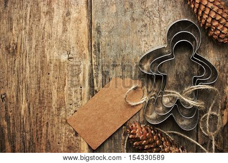 Baking Christmas gift background. Gingerbread man cookie cutter with craft paper label for text on a wooden table. Vintage celebration background